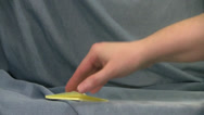 Stock Video Footage of two yellow post it notes taken from pad by hand on blue background