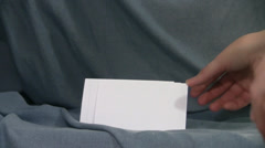 Blank 3 by 5 cards taken by hand 3 times against a blue background Stock Footage