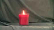 Stock Video Footage of pink candle's flame grows then is blown out against a blue background