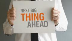 Businessman holding paper board with NEXT BIG THING AHEAD title. Stock Footage