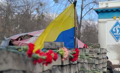 Ukraine flag and flowers near dinamo stadium in memory of euromaydan victims - stock photo