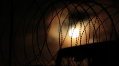 Moonscape Silhouetted by Razor Wire Fence Stock Footage