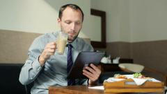 Businessman with tablet computer during breakfast in hotel room HD Stock Footage