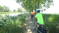Man cycling along dirt track beside river under trees Stock Footage