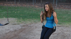 Women alone on a swingset Stock Footage