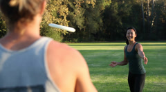 Couple throwing frisbee in park Stock Footage