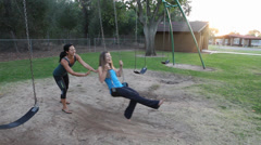Multi-ethnic pair of women at the park swinging happily together Stock Footage