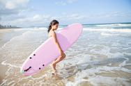 Stock Photo of young girl with surfboard
