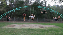 Friends swinging on swingset Stock Footage