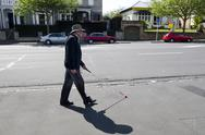 Stock Photo of blind man walks with a cane in the street