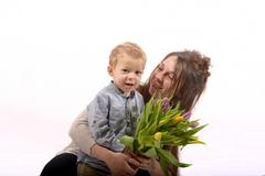 A young child offers flowers to his mom Stock Photos