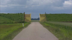 Dike coupure at Carel Coenraadpolder + zoom out country road + pan barley field Stock Footage