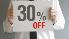 Salesman holding sale tag with thirty percent sales discount price. - stock footage