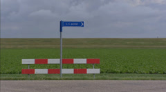 Street sign and traffic barrier in Coenraadpolder. zoom out + pan dike, polder Stock Footage