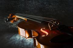 violin on concrete wall - stock photo