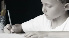 Little boy diligently writes his homework: black and white style Stock Footage