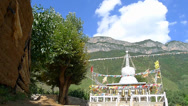 Stock Video Footage of Big tree and Tibetan Buddhism white stupa, with the beautiful Gemu holy mountain
