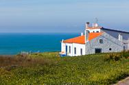 Stock Photo of turquoise sea, blue sky and white house in portugal