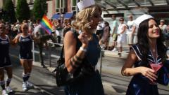 Transvestite sailor gives drink to brunette at Gay Pride. - stock footage