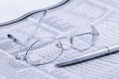 Newspaper with glasses and pen Stock Photos