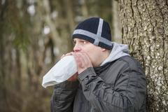 Worried man breathe into a paper bag near tree - stock photo