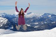 Stock Photo of young woman jumping for joy and happiness in mountains