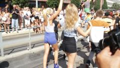 Dancing blonde girls in hotpants with fan at Gay Pride Stock Footage