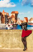 traveler woman red hair girl with camera old town gdansk - stock photo