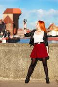 Fashionable tourist girl taking picture with camera old town gdansk Stock Photos