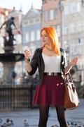 traveler woman red hair girl with smart phone old town gdansk - stock photo