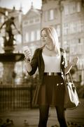 traveler young woman with smart phone old town gdansk - stock photo