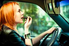 woman driver painting her lips while driving a car - stock photo