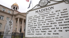 Closeup of Madison Historical Marker, State Flag, and Courthouse in WV Stock Footage