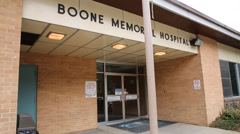 Tilt Shot From Entrance of Boone Memorial Hospital to Flags Flying on Flagpole Stock Footage