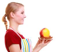 Happy housewife or chef in kitchen apron offering apple isolated Stock Photos