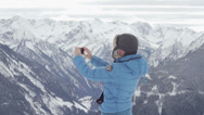 Stock Video Footage of Young woman taking photograph by cellphone in the mountains HD
