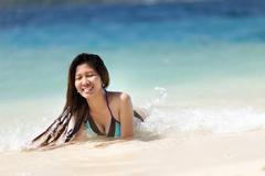 young filipina woman swimming in the sea - stock photo