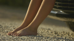 Closeup Of A Barefoot Teen Leaning Against Sports Car On A Desert Road - stock footage