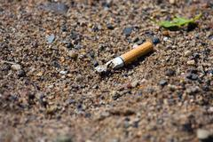 smoked cigarette on a ground - stock photo