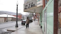 Man with Cane Passes Closed Movie Theatre Due to Economic Depression in Mt. - stock footage