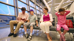 Father, mother, son and daughter sit in waiting hall of airport Stock Footage
