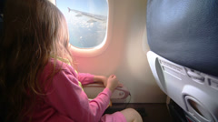 Little girl in pink clothes looks out window in aircraft Stock Footage
