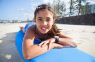 Stock Photo of cute young girl lying on surfboard