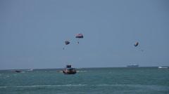 People enjoying holiday at sea parachute Stock Footage