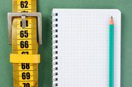 Stock Photo of meter belt slimming and notepad on the green background
