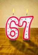 Burning birthday candles number 67 Stock Photos