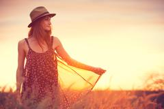 beautiful woman in golden field at sunset - stock photo