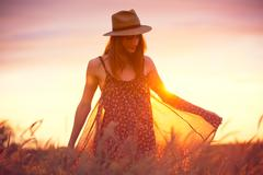 Beautiful woman in golden field at sunset Stock Photos