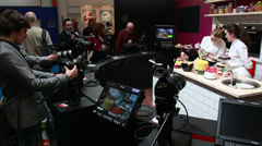 HD cameras testing on two models (cooking backdrop) at BVE in London Stock Footage