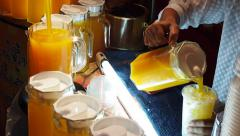 Vendor Pouring Orange Juice Into Cup in Traditional Street Food Market, Thailand Stock Footage